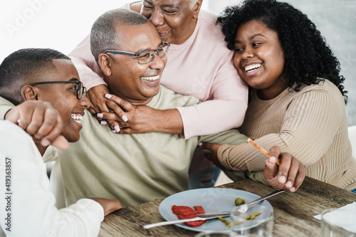 Fototapeta Happy black family eating lunch at home - Father, daughter, son and mother having fun together sitting at dinner table - Main focus on man face obraz