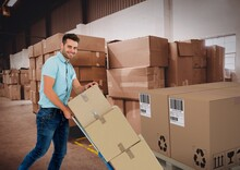 Composition Of Delivery Man With Trolley Full Of Cardboard Boxes, Warehouse In Background