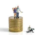 Miniature Tiny People Toys Photography. A Generous Man Standing On A Pile Of Coins, Giving Money Cash To A Beggar Poor Man, Isolated On White Background.