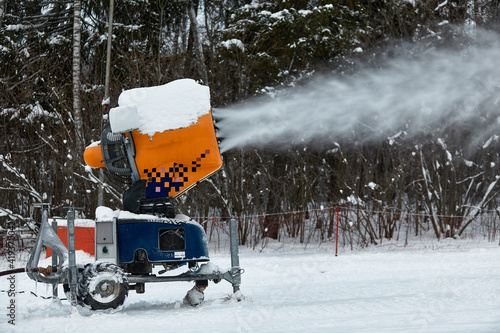 Snow cannon spraying out a fresh dusting of snow on the ski slopes Fotobehang
