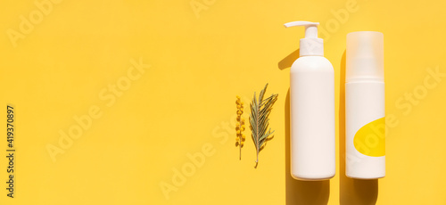 Clean white cosmetic containers bottles with mimosa flowers on yellow background flat lay top view. Blank label package for branding mock-up. Spring cosmetics concept. Natural organic beauty product