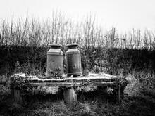 Rusted Vintage Milk Churns On A Wooden Platform