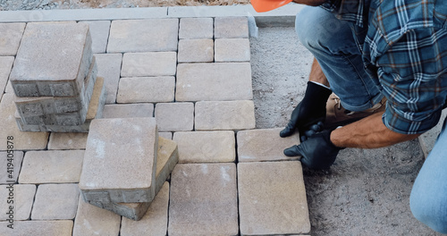 Fotografie, Obraz cropped view of man working with paving stones on construction site