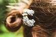 Małe białe kwiaty wplecione we włosy kobiety.