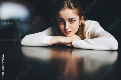Fototapeta Young thoughtful woman resting head on hands at table obraz