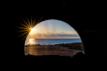 View Of A Beautiful Sunrise Over The Ocean Through The Window Of A Pop Up Roof In A Camper Van