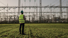 Electrical Engineer Wearing A Helmet And Safety Vest Working With Tablet Near High Voltage Electrical Lines Power Station During Sunset