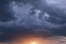 Dark Storm Cumulus Clouds With Yellow Orange Sun And Sunlight On Sunset, Sunrise