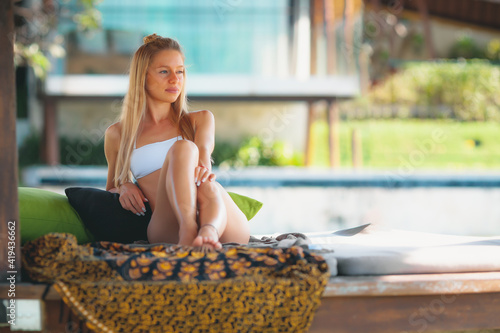 Fototapeta Young attractive blonde girl with perfect sport body relaxing at resort lounger