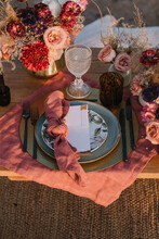 From Above Of Wooden Table Setting With Cutlery On Plates Served On Cloth Near Colorful Bouquets Of Flowers With Wineglasses During Wedding Celebration