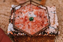 From Above Of Gold Ring With Green Gemstone Placed In Box With Pink Decoration Placed On Pillow With Gold Sequin During Wedding Celebration On Blurred Background