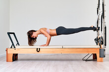Side View Of Young Fit Sportswoman In Active Wear Standing In Plank Pose During Training On Professional Sports Apparatus
