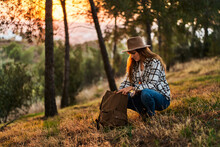 Side View Full Length Serene Young Female In Casual Wear And Hat Hunkering Down And Opening Backpack While Having Break In Verdant Woods At Sunset