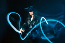 Side View Of Unrecognizable Female Wearing Modern VR Headset And Playing With Motion Game Controller In Blue Neon Lights While Exploring Cyberspace