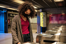Young Ethnic Curly Haired Female Passenger In Protective Mask Standing Near Turnstile And Scanning Ticket While Entering Subway Station