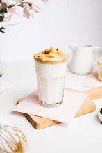Teaspoon With Sweet Whipped Foam Above Fresh Yummy Latte Served On Wooden Cutting Board In Modern Light Kitchen
