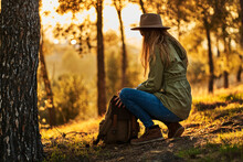 Side View Full Length Serene Unrecognizable Young Female In Casual Wear And Hat Hunkering Down And Opening Backpack While Having Break In Verdant Woods At Sunset
