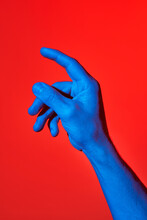 Man's Blue Hand Pointing Upwards Over Red Background. Isolated Vertical Photo