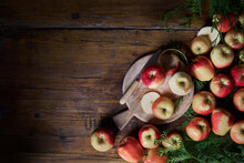 Top View Of Fresh Ripe Whole And Sliced Red Apples With Cutting Board And Knife Arranged On Rustic Wooden Table With Green Foliage