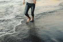 Crop Anonymous Barefoot Male Traveler In Jeans Walking On Sandy Beach Near Waving Sea At Sunset Time