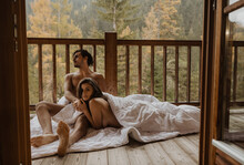 Romantic Undressed Couple Lying On Cozy Blanket And Cuddling On Wooden Cottage Terrace Against Deciduous Forest On Autumn