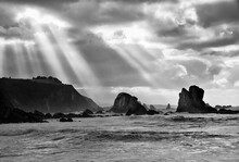 Rays Of Light Breaking Through The Storm Clouds Over The Beach Of Silencio In Asturias