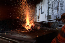 Crop Unrecognizable Male Blacksmith Heating Metal Rod On Burning Flame During Forging Process In Workshop