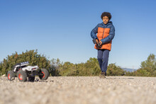 Cute Afro Kid With Curly Hair Operating Radio Controlled Car In The Park