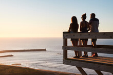 Full Body Back View Of Tourists Standing On Wooden Platform And Admiring Calm Sea During Sundown