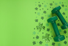 Two Heavy Dumbbells And Irish Shamrock Leaf Clover. Healthy Fitness Gym Flat Lay Composition Concept For St. Patrick's Day. Copyspace On Green Background.