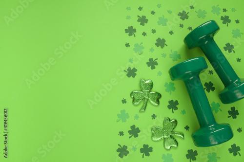 Obraz na plátně Two heavy dumbbells and Irish shamrock leaf clover