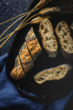 From Above Of Appetizing Crusty Bread Near Wheat Spikes And Dark Fabric On Table