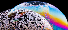 Panoramic View Of Closeup Bubble Textured Backdrop Representing Colorful Planets With Wavy Lines On Round Shaped Surface On Black Background