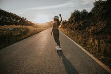 Back View Sporty Female In Trendy Wear Riding Cruiser Board Along Empty Asphalt Road In Summer Countryside On Sunny Day