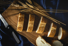 Top View Of Pieces Of White Bread Near Knife And Wheat Spikes On Wooden Board