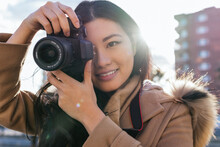 Ethnic Young Happy Asian Female Photographer Shooting Photo On Professional Photo Camera On City Street