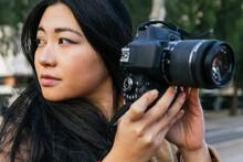 Ethnic Asian Female Photographer Shooting Photo On Professional Photo Camera On City Street
