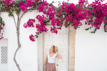 Young Gorgeous Woman In Stylish Clothes And Straw Hat Standing Near Cozy Old White House With Blooming Tree During Vacation In Algarve, Portugal