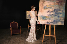 Full Body Of Charming Young Slender Female In Elegant Maxi Bridal Gown Standing Near Easel With Painting In Dark Art Studio