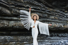 Elegant Young Slim Female Model In White Suit With Wings Shaped Tassel Sleeves And Hat Outstretching Arms While Standing Against Rough Rocky Formation