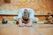 Anonymous Flexible Male With Tattoo Practicing Yoga Between Buddha Statuette And Bowl Gong Against Stone Wall