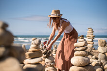 Cheerful Young Female Traveler In Stylish Clothes Standing Straw Hat Creating Stone Pyramids While Enjoying Sunny Summer Day On Sandy Beach Of Waving Ocean In Vila Nova De Milfontes, Portugal
