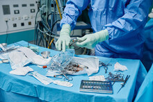 Crop Anonymous Surgeon In Gown And Latex Gloves Choosing Various Instruments Scattered On Sterile Field While Performing Operation In Hospital