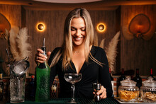 Alluring Young Female Bartender With Long Blond Hair Preparing Alcohol Drink Cocktail At Counter