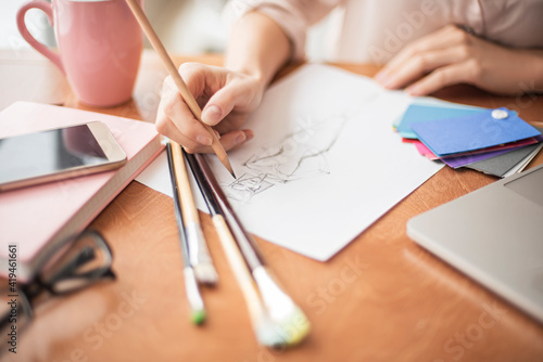 Papel de parede Young woman designer in cafe sitting with cup of coffee drawing new dress for co