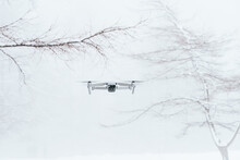 Contemporary White UAV Flying Over Snowy Glade In Frozen Winter Woods In Daylight