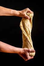 Faceless Woman Kneading And Stretching Bunch Of Heavy Bread Dough On Black Background