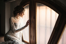 Side View Of Attractive Young Woman In Elegant Lace Bridal Gown And Wreath Sitting Near Window In Vintage Styled Room