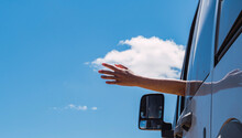 Low Angle Of Crop Unrecognizable Person Sticking Out Arm Out Of Car Window On Background Of Blue Sky And Enjoying Freedom During Summer Vacation