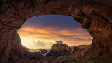 Spectacular Landscape Of Island Of Pancha Seen From Rough Rocky Cave With Small House Against Cloudy Sundown Sky In Ribadeo In Spain